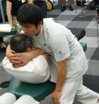胸椎屈曲CMT(チェスタードロップ)を実演しているところ