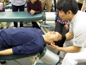 頸椎の緩め方を実演する安藤院長。2017年のセミナーの様子。