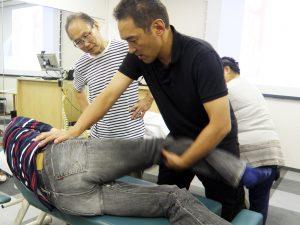 股関節を動かしながら、殿筋や側腹部の筋緊張を緩和していく