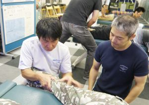 膝の裏のこわばりを伸長していくイメージを説明する安藤先生